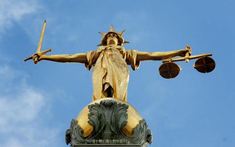 Lady Justice, holding scales and a sword, on top of the Central Criminal Court - PA