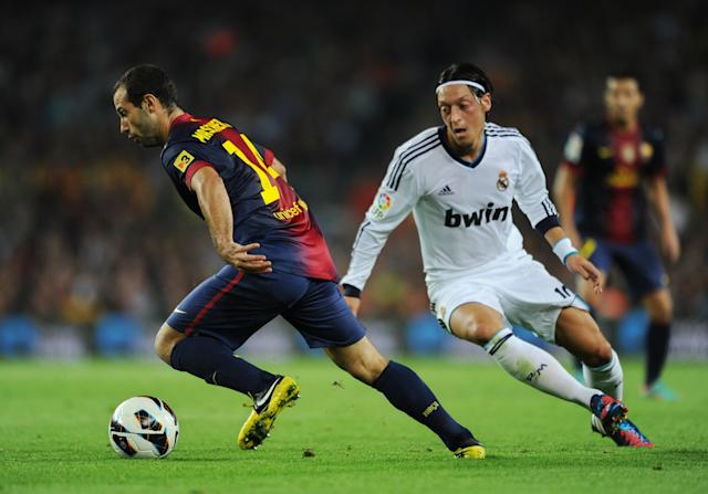 BARCELONA, SPAIN - OCTOBER 07: Javier Mascherano (L) of Barcelona shields Mesut Ozil of Real Madrid from the ball during the la Liga match between FC Barcelona and Real Madrid at the Camp Nou stadium on October 7, 2012 in Barcelona, Spain. (Photo by Jasper Juinen/Getty Images)