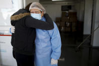 COVID-19 patient Claudia Brigando, right, embraces her daughter Marina Peralta, after being discharged from a hospital in Mar del Plata, Argentina, Saturday, Oct. 10, 2020. Mar del Plata, which at the start of the pandemic reported one case a day or less, is now reporting an average of 300 confirmed coronavirus cases a day. (AP Photo/Natacha Pisarenko)