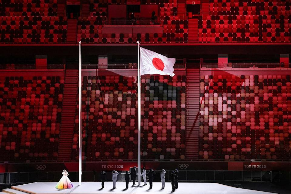 People stand on stage alongside the Japanese flag