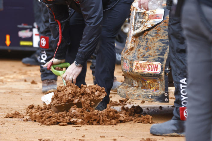 A crew member shovels up mud that was removed from the front of a truck during a heat race for a NASCAR Truck Series race on Saturday, March 27, 2021, in Bristol, Tenn. (AP Photo/Wade Payne)