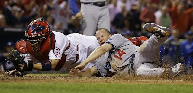 St. Louis Cardinals catcher Yadier Molina tags out Los Angeles Dodgers' Mark Ellis at home during the 10th inning of Game 1 of the National League baseball championship series Friday, Oct. 11, 2013, in St. Louis. (AP Photo/Jeff Roberson)