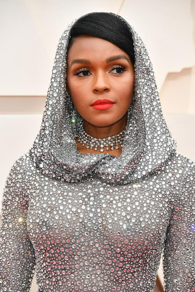 """It's hard to compete with a bedazzled hood, but Monet's bright red lips draw the attention right to her face, and as always, her lashes (courtesy of <a href=""""https://lashify.com/collections/all/products/a-gossamer"""" rel=""""nofollow"""">Lashify</a>) are on point."""