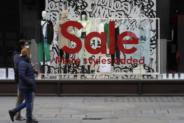 Pedestrians walk past a Sale sign in the window of a closed shop on Oxford Street in London, Saturday, Dec. 26, 2020. London is currently in Tier 4 with all non essential retail closed and people have been asked to stay at home, on what is usually one of the busiest retail days of the year with the traditional Boxing Day sales in shops. (AP Photo/Kirsty Wigglesworth)