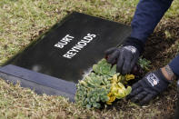 Flowers are placed in front of a temporary headstone for the late actor Burt Reynolds in the Garden of Legends section of Hollywood Forever cemetery, Thursday, Feb. 11, 2021, in Los Angeles. Reynolds' cremated remains were moved from Florida to Hollywood Forever, where a small ceremony was held Thursday. A permanent gravesite will be put up for Reynolds in a few months. (AP Photo/Chris Pizzello)