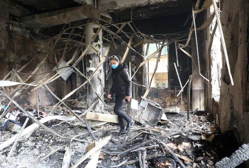 A woman walks inside the damaged municipality building that was set ablaze overnight, in the aftermath of protests against the lockdown and worsening economic conditions, amid the spread of the coronavirus disease (COVID-19), in Tripoli