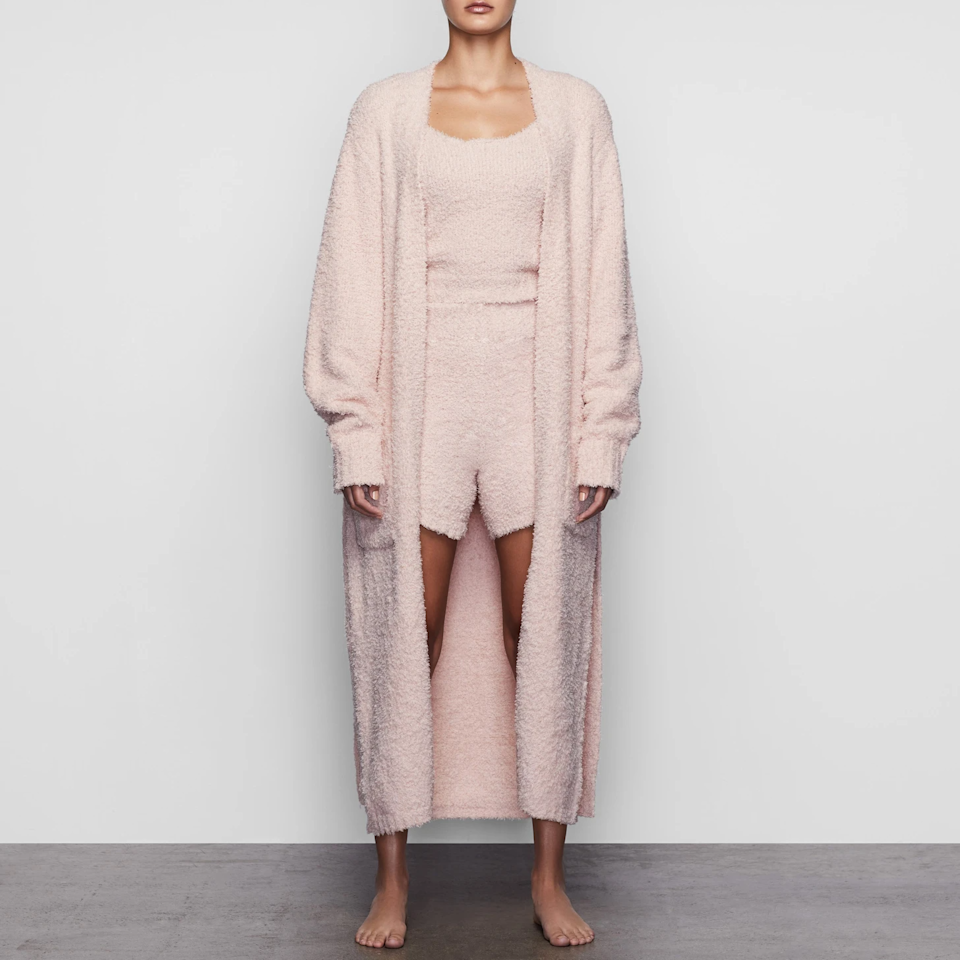 """<h2>Skims Cozy Knit Robe</h2><br>We wouldn't expect anything less than literally the chicest robes from the loungewear queen herself. This one from Skims recently restocked <a href=""""https://skims.com/collections/loungewear#cozy"""" rel=""""nofollow noopener"""" target=""""_blank"""" data-ylk=""""slk:Cozy collection"""" class=""""link rapid-noclick-resp"""">Cozy collection</a> is the perfect longer-length and comes in a range of KKW's signature muted hues. We also recommend the <a href=""""https://skims.com/products/waffle-robe-mineral"""" rel=""""nofollow noopener"""" target=""""_blank"""" data-ylk=""""slk:Waffle Robe"""" class=""""link rapid-noclick-resp"""">Waffle Robe</a>. <br><br><br><strong>Skims</strong> Cozy Knit Robe, $, available at <a href=""""https://go.skimresources.com/?id=30283X879131&url=https%3A%2F%2Fskims.com%2Fproducts%2Fcozy-knit-robe-dusk"""" rel=""""nofollow noopener"""" target=""""_blank"""" data-ylk=""""slk:Skims"""" class=""""link rapid-noclick-resp"""">Skims</a>"""