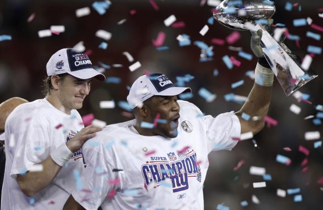 New York Giants quarterback Eli Manning, left, and Michael Strahan celebrate their 17-14 win over the New England Patriots in Super Bowl XLII at University of Phoenix Stadium on Sunday, Feb. 3, 2008, in Glendale, Ariz. (AP/Julie Jacobson)