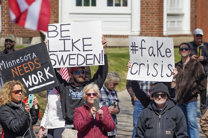 """People protesting Minnesota's stay-at-home order with a """"Be Like Sweden"""" sign outside the governor's residence in April 2020."""