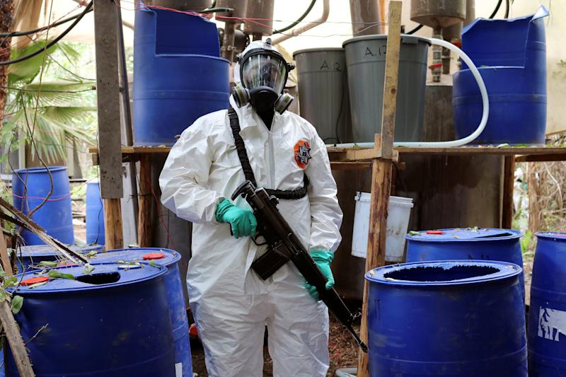 A member of the State Police in full protective gear keeps watch at a methamphetamine drug lab discovered in a joint operation in the area of El Dorado, in Sinaloa state, Mexico June 4, 2019. Picture taken June 4, 2019. REUTERS/Jesus Bustamante