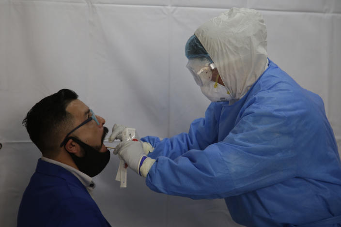 A health worker wears PPE while administering a swab test to detect COVID-19. Photo: Eyepix/SIPA USA/PA Images