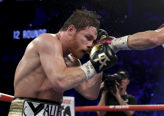 Canelo Alvarez takes a punch from Gennady Golovkin in the 10th round during a middleweight title boxing match, Saturday, Sept. 15, 2018, in Las Vegas. (AP Photo/Isaac Brekken)