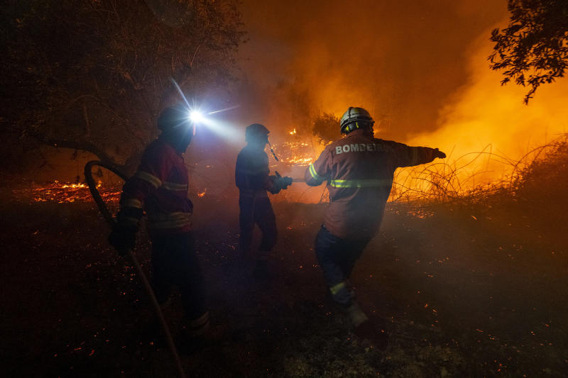 Fighters try to extinguish a wildfire near Cardigos village, in central Portugal on Sunday, July 21, 2019. About 1,800 firefighters were struggling to contain wildfires in central Portugal that have already injured people, including several firefighters, authorities said Sunday. (AP Photo/Sergio Azenha)