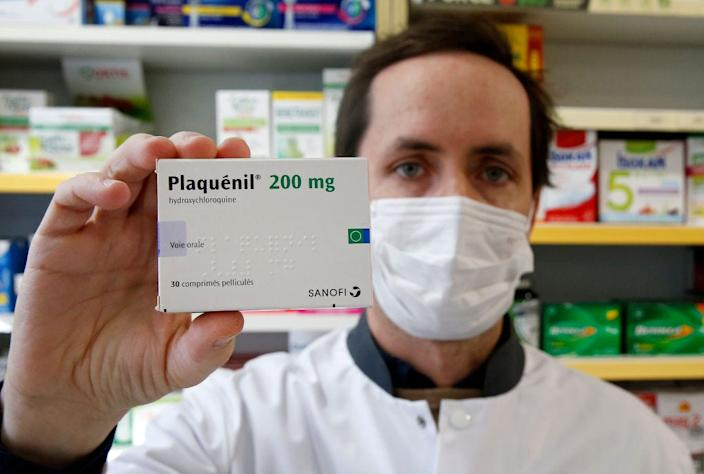 A pharmacy worker shows a box of Plaquenil, or hydroxychloroquine in Paris.