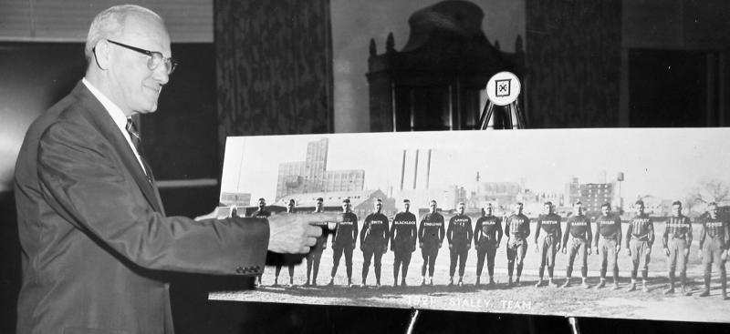FILE - In this undated file photo, Chicago Bears founder George Halas points to a picture of the 1920 Decatur Staleys football club, which later became the Bears. The first season, 1920, the American Professional Football Association had 14 teams including the Decatur Staleys.  (The News-Gazette via AP, File)