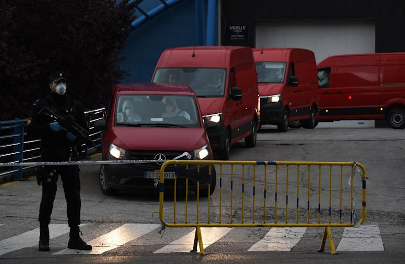 Red vans drop off bodies to the makeshift morgue on Tuesday. Source: Getty