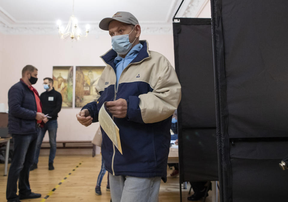 A man, wearing face masks to protect against coronavirus leaves the polling booth at a polling station during parliamentary elections in Vilnius, Lithuania, Sunday, Oct. 11, 2020. Polls opened Sunday for the first round of national election in Lithuania, where voters will renew the 141-seat parliament and the ruling four-party coalition is widely expected to face a stiff challenge from the opposition to remain in office. (AP Photo/Mindaugas Kulbis)