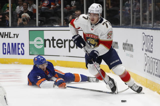Florida Panthers center Frank Vatrano (77) looks to pass as he skates over the stick of New York Islanders defenseman Adam Pelech (3) behind the Islanders' net during the first period of an NHL hockey game Saturday, Oct. 12, 2019, in Uniondale, N.Y. (AP Photo/Kathy Willens)
