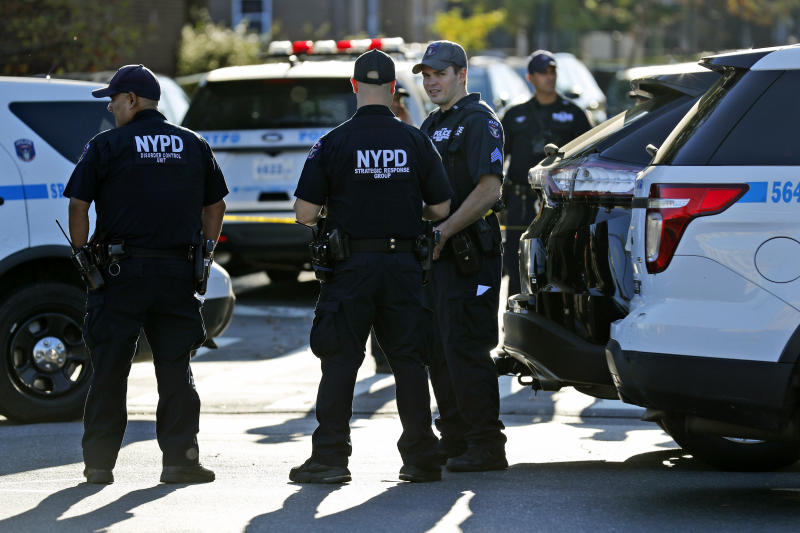 Emergency personnel stand near the scene of a fatal shooting of a police officer in the Bronx borough of New York, Sunday, Sept. 29, 2019. (AP Photo/Seth Wenig)