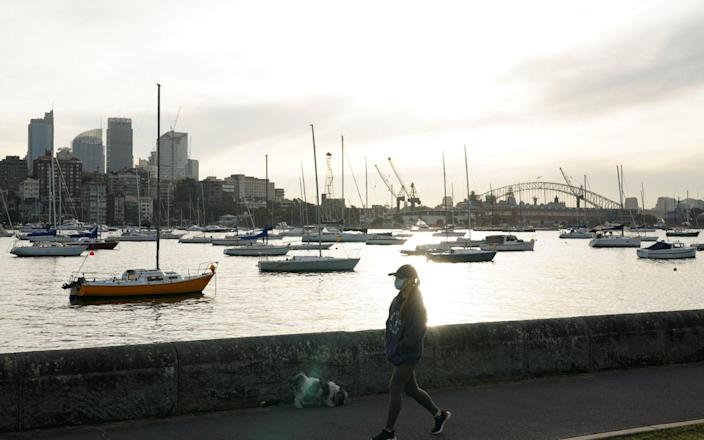 A woman wearing a protective face mask walks along a waterfront path during a lockdown to curb the spread of a coronavirus disease (COVID-19) outbreak in Sydney, Australia, J - Reuters