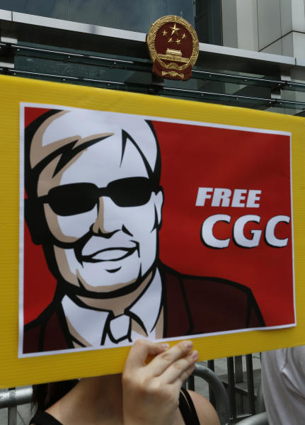 """An image featuring blind Chinese activist Chen Guangcheng is shown by a protester during a rally in front of the Chinese central government's liaison in Hong Kong Friday, May 4, 2012. Chen at the center of a diplomatic standoff between the United States and China said Friday his situation is """"dangerous,"""" and that American officials have been blocked from seeing him for two days and friends who have tried to visit have been beaten up. (AP Photo/Vincent Yu)"""