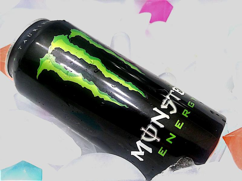 A can of Monster Energy resting on a bed of ice cubes.