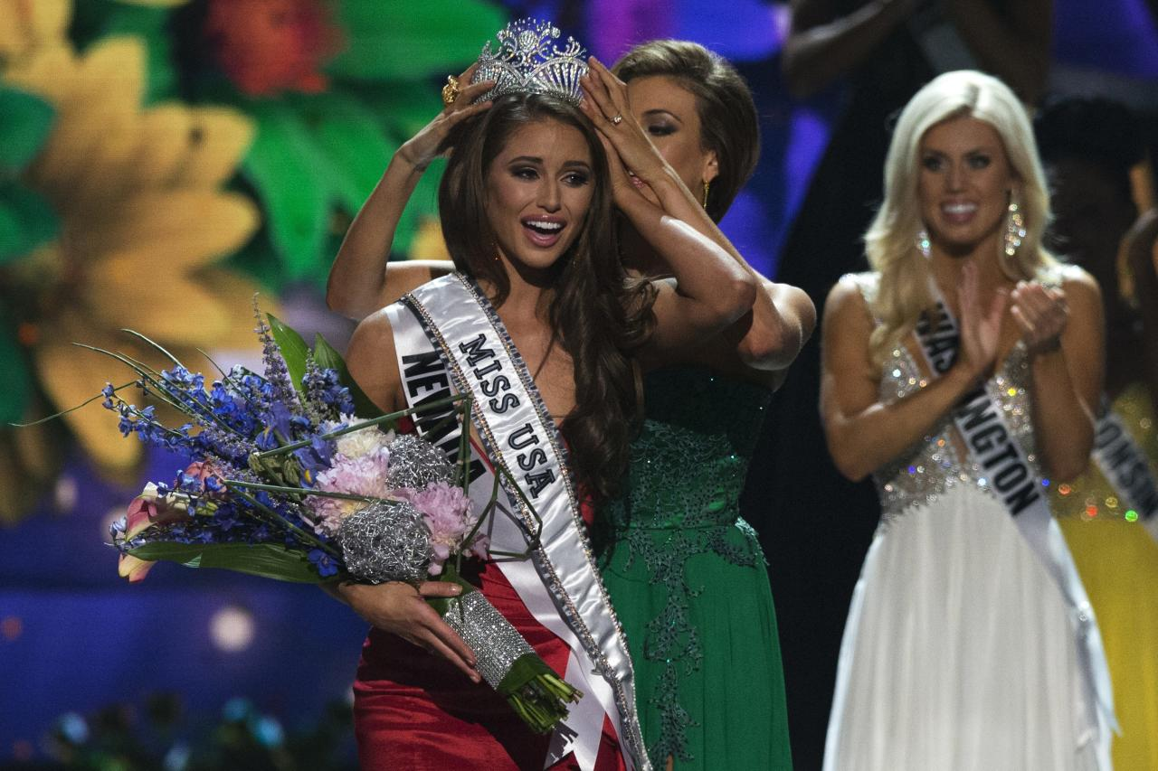 Miss Nevada Nia Sanchez is crowned by Miss USA 2013 Erin Brady after winning the 2014 Miss USA beauty pageant in Baton Rouge, Louisiana June 8, 2014. Fifty-one state titleholders compete in the swimsuit, evening gown and interview categories for the title of Miss USA 2014 during the 63rd annual Miss USA competition. Miss Washington Allyson Rowe is seen in the background REUTERS/Adrees Latif (UNITED STATES - Tags: ENTERTAINMENT SOCIETY) ATTENTION EDITORS - FOR EDITORIAL USE ONLY. NOT FOR SALE FOR MARKETING OR ADVERTISING CAMPAIGNS