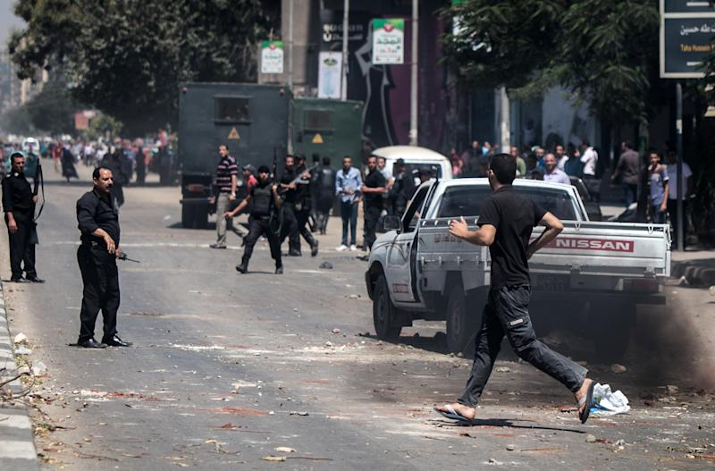 Civilians runs across a street in Cairo as policemen gather during clashes with Muslim Brotherhood supporters following a rally marking the first anniversary of a brutal Cairo crackdown, on August 14, 2014 (AFP Photo/Mohamed El-Shahed)