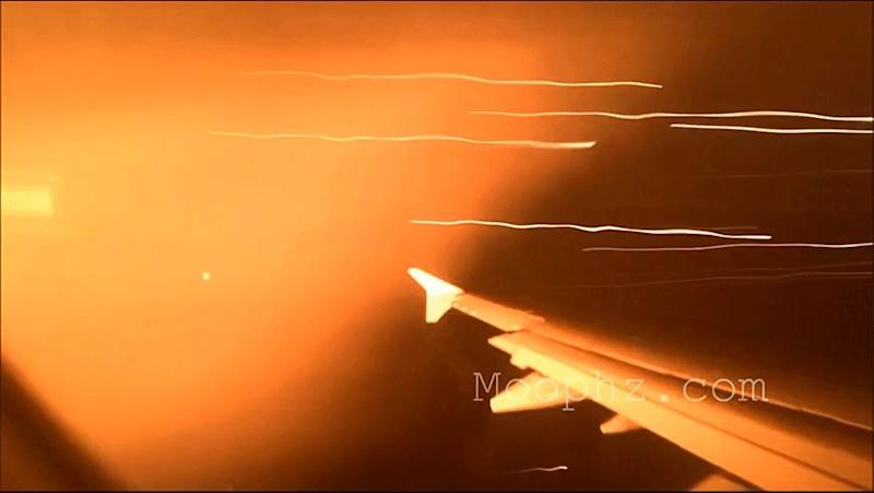 A passenger captures flames shooting from a plane engine. Photo: Youtube/Moophz.com