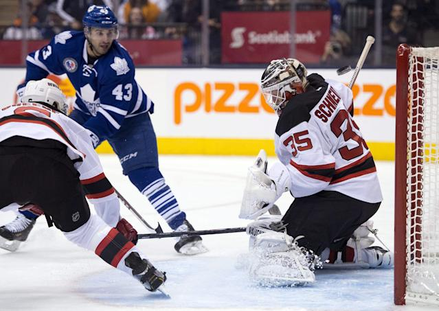 New Jersey Devils goaltender Cory Schneider makes a save on Toronto Maple Leafs center Nazem Kadri (43) as defenseman Andy Greene helps out during during the second period of an NHL hockey game, Friday, Nov. 8, 2013 in Toronto. (AP Photo/The Canadian Press, Frank Gunn)