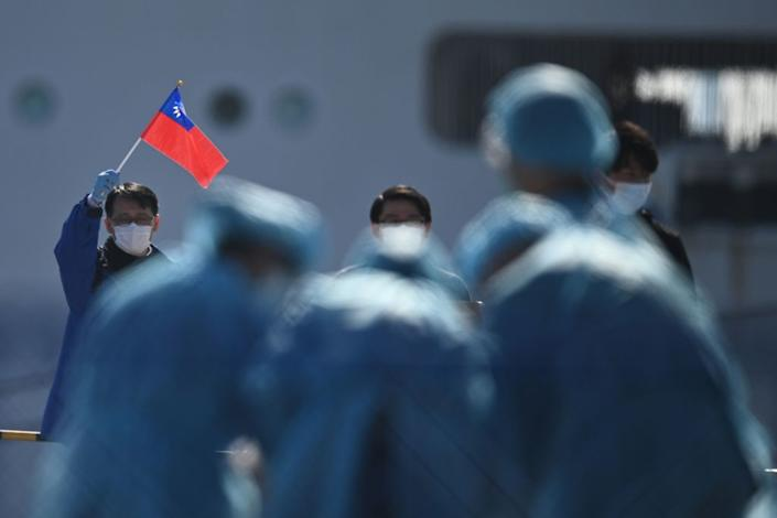 A man holds a Taiwan flag as passengers disembark from the Diamond Princess cruise ship due to fears of COVID-19 in Yokohama, Japan on Feb. 21, 2020. | Philip Fong—AFP/Getty Images