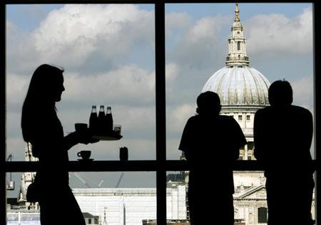 Visitors admire St. Paul's Cathedral from the restaurant floor of the Tate Modern gallery in London