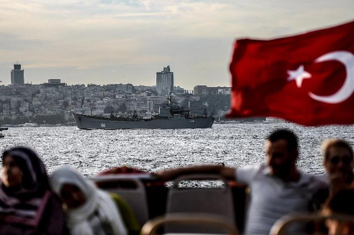 A Turkish flag flies on a ferry as Russian warship, the BSF Saratov 150, is seen sailing through the Bosphorus off Istanbul en route to the eastern Mediterranean sea (AFP Photo/OZAN KOSE)