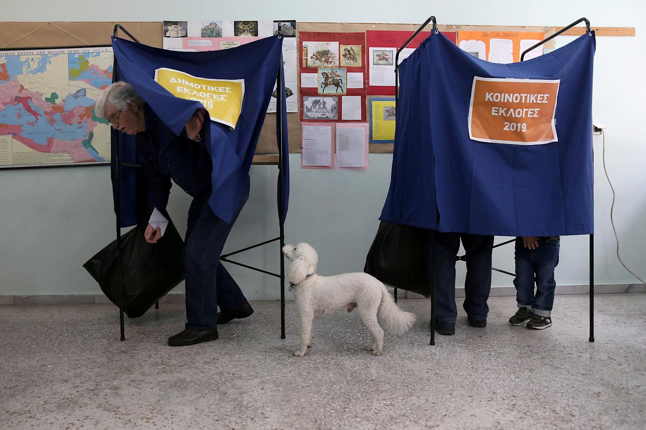 A dog stands next to its owner as he exits the polling booth, during the European Parliament and local elections at a polling station in Athens, Greece, May 26, 2019. REUTERS/Costas Baltas     TPX IMAGES OF THE DAY