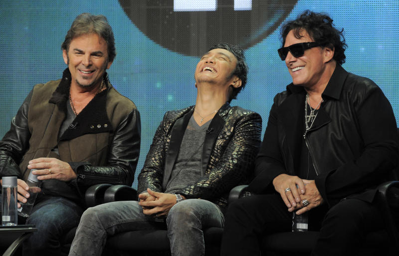 "Jonathan Cain, left, Arnel Pineda, center, and Neal Schon of the rock band Journey take part in a panel discussion on the Independent Lens documentary ""Don't Stop Believin': Everyman's Journey,"" at the PBS Summer 2013 TCA press tour at the Beverly Hilton Hotel on Tuesday, Aug. 6, 2013 in Beverly Hills, Calif. (Photo by Chris Pizzello/Invision/AP)"