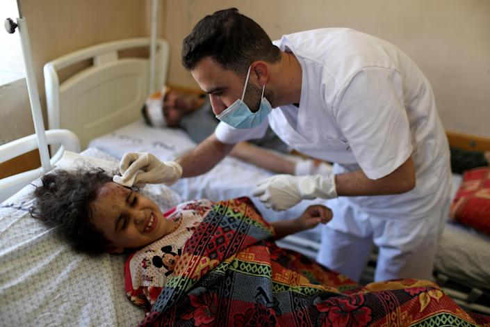 Palestinian girl Suzy Eshkuntana, 6, is treated by a medic at a hospital after being pulled from the rubble of a building   hit by an Israeli airstrike, as her father watches from the next bed, in Gaza City, May 16, 2021. / Credit: MOHAMMED SALEM/REUTERS