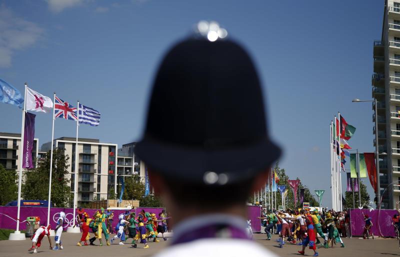 A police officer watches the Olympic Team Welcome Ceremony at the Athletes' Village at the Olympic Park, Sunday, July 22, 2012, in London. Opening ceremonies for the 2012 London Olympics will be held Friday, July 27. (AP Photo/Jae C. Hong)