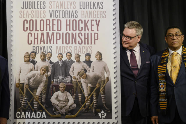 Doug Ettinger, left, President and CEO of Canada Post, and Craig Smith, President of The Black Cultural Society, unveil Canada Post's new stamp honouring the Colored Hockey Championship and the all-Black hockey teams in the Maritimes between 1895 and the early 1930s during an event at the Black Cultural Center in Halifax, Nova Scotia, Thursday, Jan. 23, 2020. (Darren Calabrese/The Canadian Press via AP)