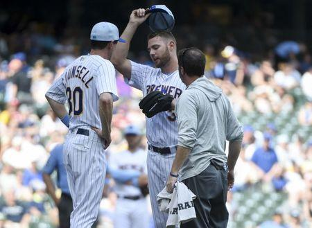 Jun 17, 2018; Milwaukee, WI, USA; Milwaukee Brewers manager Craig Counsell talks to pitcher Adrian Houser (37) who fell ill during the game against the Philadelphia Phillies in the eighth inning at Miller Park. Mandatory Credit: Benny Sieu-USA TODAY Sports