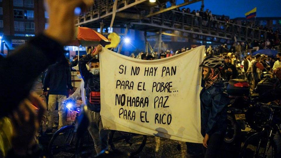 """Protesters hold up a sign reading """"When there's no bread for the poor, there's no peace for the rich"""""""