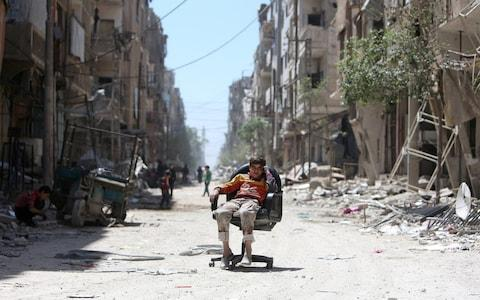 A boy sits on a chair along a damaged street in Douma, which was allegedly hit with a chlorine attack - Credit: ALI HASHISHO/REUTERS