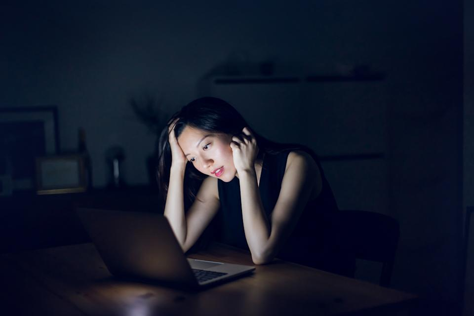 Stressed and frustrated businesswoman working on laptop till late at work