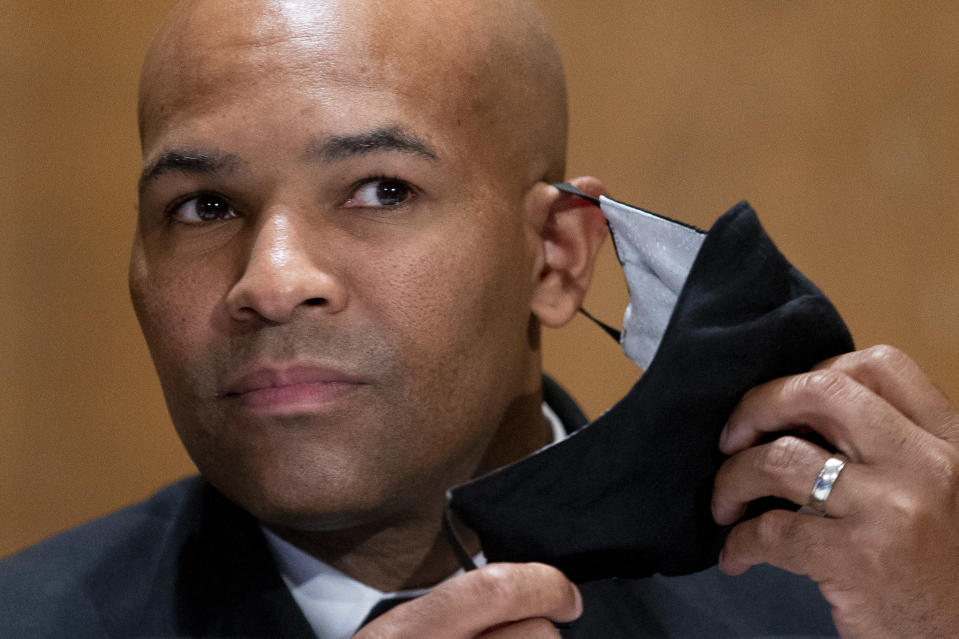 Surgeon General Jerome Adams takes off his face mask as he appears before a Senate Health, Education, Labor and Pensions Committee hearing to discuss vaccines and protecting public health during the coronavirus pandemic on Capitol Hill, Wednesday, Sept. 9, 2020, in Washington. (Michael Reynolds/Pool via AP)
