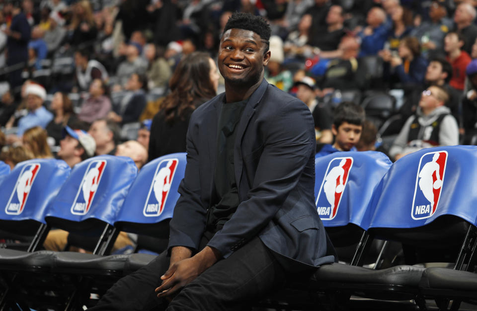 Injured New Orleans Pelicans forward Zion Williamson smiles as he jokes with fans while waiting on the team bench for the second half of the team's NBA basketball game against the Denver Nuggets on Wednesday, Dec. 25, 2019, in Denver. The Pelicans won 112-100. (AP Photo/David Zalubowski)