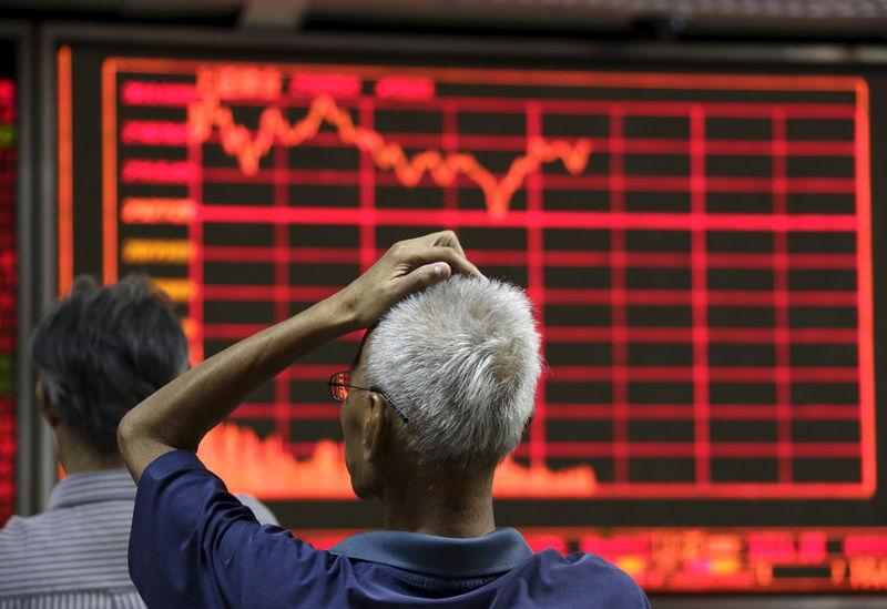 An investor looks at an electronic board at a brokerage house in Beijing