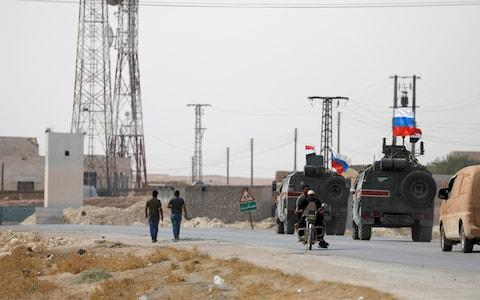 Russian and Syrian forces driving near Manbij on Tuesday morning - Credit: OMAR SANADIKI/ REUTERS
