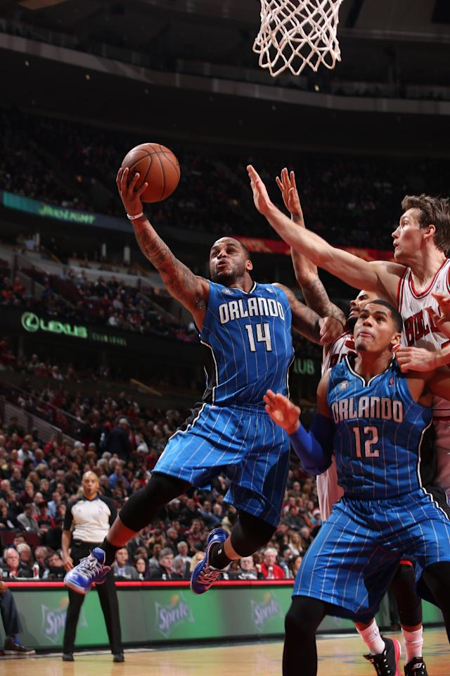 CHICAGO, IL - DECEMBER 16: Jameer Nelson #14 of the Orlando Magic goes to the basket over teammate Tobias Harris #12 and Mike Dunleavy #34 of the Chicago Bulls on December 16, 2013 at the United Center in Chicago, Illinois. (Photo by Gary Dineen/NBAE via Getty Images)