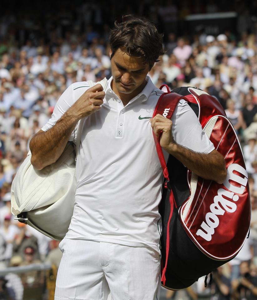 Switzerland's Roger Federer leaves the court after being defeated by France's Jo-Wilfried Tsonga in their match at the All England Lawn Tennis Championships at Wimbledon, Wednesday, June 29, 2011. (AP Photo/Kirsty Wigglesworth)