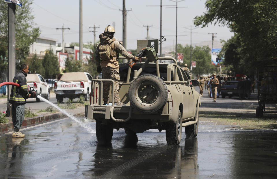 Afghan security personnel leave the scene of a roadside bomb explosion in Kabul, Afghanistan, Sunday, June 6, 2021. (AP Photo/Rahmat Gul)