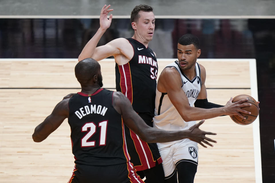 Brooklyn Nets guard Timothe Luwawu-Cabarrot, right, looks for an opening past Miami Heat center Dewayne Dedmon, left, and forward Duncan Robinson, center, during the first half of an NBA basketball game, Sunday, April 18, 2021, in Miami. (AP Photo/Wilfredo Lee)